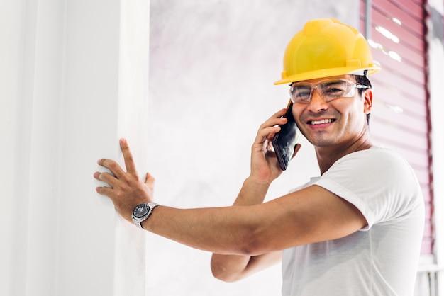 Молодой инженер-строитель в желтом шлеме работает и ищет работу для планирования проекта на стройке дома Premium Фотографии