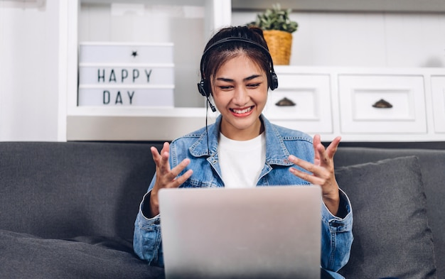 若い笑顔幸せな美しいアジアの女性の自宅でラップトップコンピューターの作業とビデオ会議の会議を使用してリラックスしました。創造的な少女は、ヘッドセットと話します。在宅勤務のコンセプト Premium写真