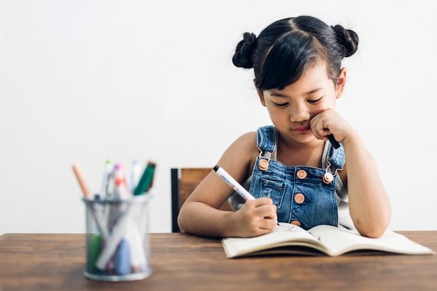 Школьница маленькая девочка учиться и писать в тетради с карандашом, делать домашнее задание на дому. концепция образования Premium Фотографии