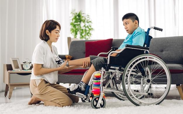 アジアの理学療法士介護者を支援し、リハビリクリニックで車椅子に座って演習を行うことによって特別な障害児の健康問題で遊んでいます。障害ケアの概念 Premium写真