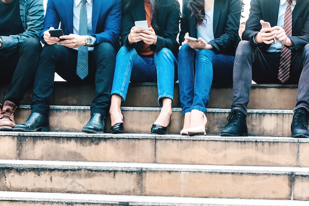 ビジネスマンのグループがスマートフォンの技術を一緒に利用している Premium写真