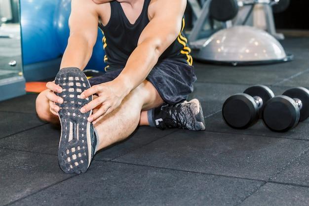 フィットネスジムで運動をウォームアップするために彼女の足を伸ばして男 Premium写真