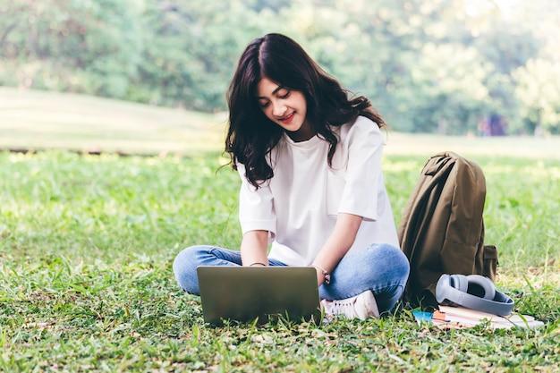 女性が公園の芝生の上に座っているラップトップコンピューターでリラックス Premium写真
