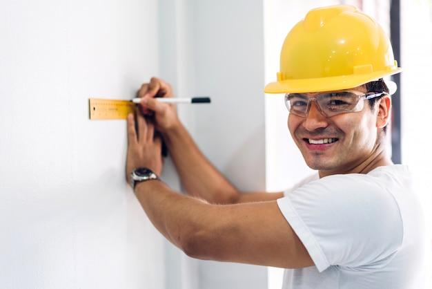 ホームサイトの構築でプロジェクトを計画するための仕事と探している黄色いヘルメットの若い建設エンジニア Premium写真