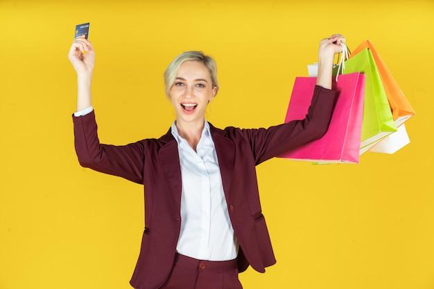 クレジットカードで買い物袋を押しながら黄色の買い物を楽しんでいる美しい女性の肖像画 Premium写真