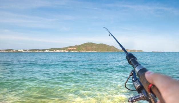 漁師は海洋の海で魚と戦っている釣竿を保持します。スポーツ活動または漁業と水産養殖。 Premium写真