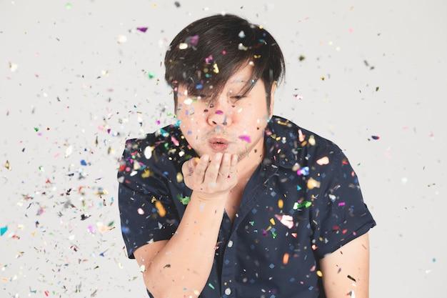 Азиатский человек с удовольствием с красочными конфетти на серый. Premium Фотографии