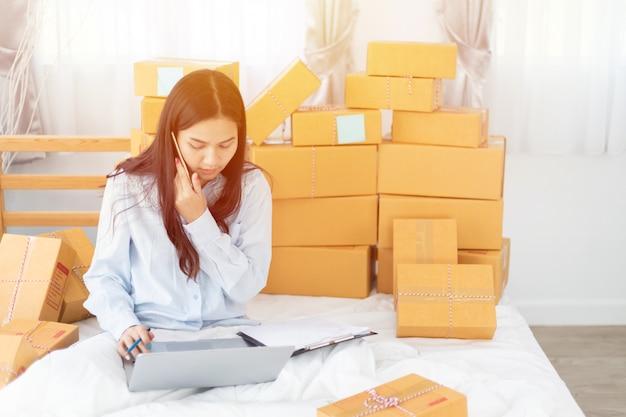Азиатская деловая женщина-владелец малого и среднего бизнеса онлайн с помощью ноутбука получает заказ от клиента с посылкой Premium Фотографии