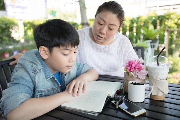 母親の家庭であなたの宿題を教えて学ぶアジアの少年 Premium写真