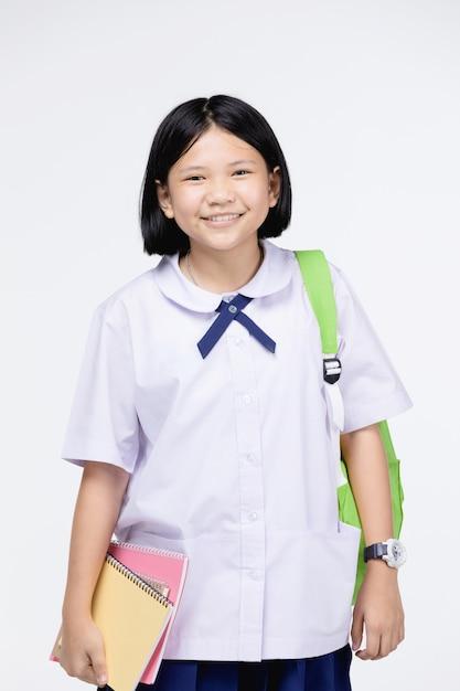 灰色の文房具と学生の制服を着たかわいい女の子 Premium写真