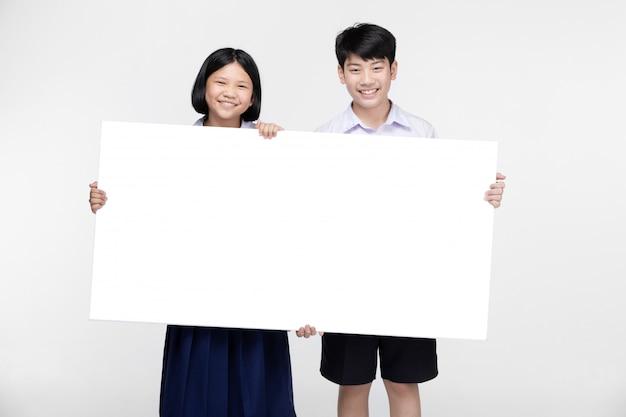 Милые азиатские дети в форме студента с белой доской. Premium Фотографии
