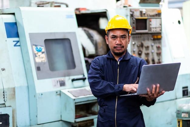 ハード帽子のアジアのチーフエンジニアであり、古い工場設備で機械部品に関するコンピューターラップトップに取り組んでいます。 Premium写真