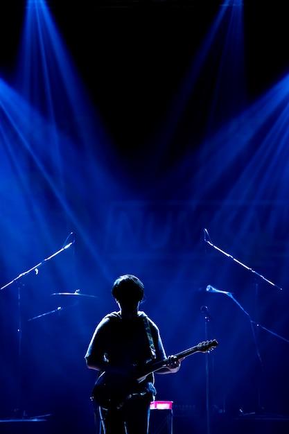 アジアのミュージシャンがスポットライトとレンズフレアと黒の背景にギターを弾く Premium写真