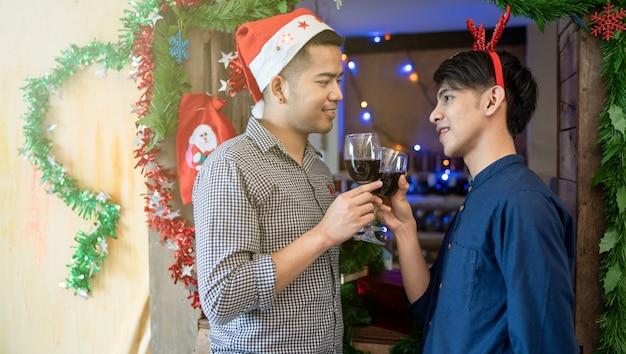 Лгбт мужские пары пьют вино празднуют рождество Premium Фотографии