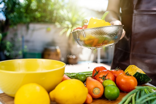 彼は果物と野菜を洗っています。 Premium写真
