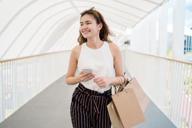 Красивая девушка с длинными волосами она с удовольствием делает покупки в уличном торговом центре Premium Фотографии