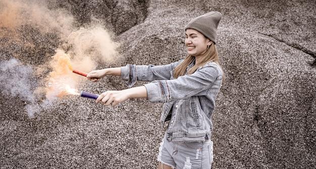 美しい女性彼女はロックグランドキャニオンの場所で花火の煙の色を再生しています。 Premium写真