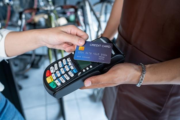 自転車屋の所有者この店は小さなビジネスです。クレジットカードによる支払いを受け入れる Premium写真
