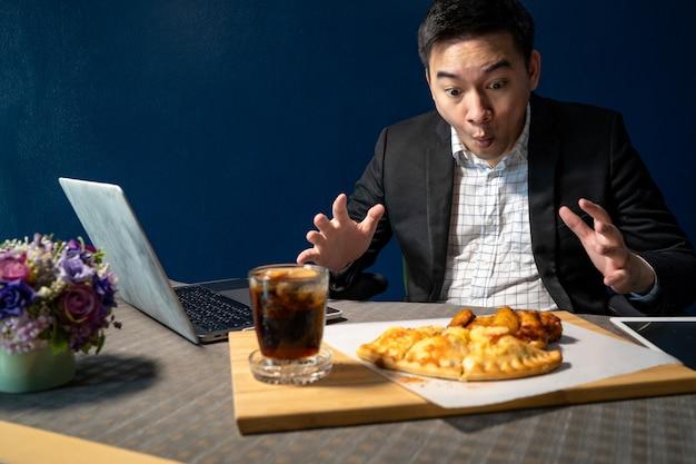 ビジネスマンは、机の上にピザとバーベキューチキンレッグを食べています。 Premium写真