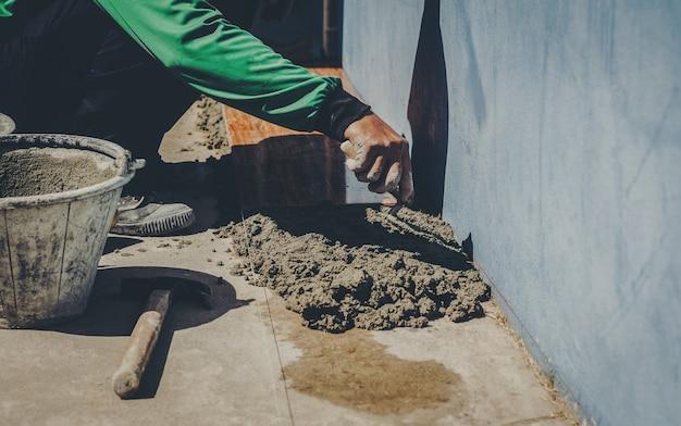 Промышленный рабочий с штукатурными инструментами ремонтирует дом Premium Фотографии
