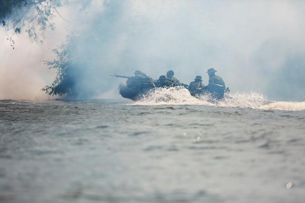 Спецназы мужчины в камуфляжной форме играют на байдарках. Premium Фотографии