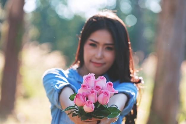 背景のボケ味を持つ庭で花を持って笑顔の遊び心のあるかわいい女の肖像画。 Premium写真