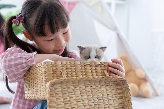 友情の概念、自宅の木製バスケットで猫と遊ぶ少女。 Premium写真