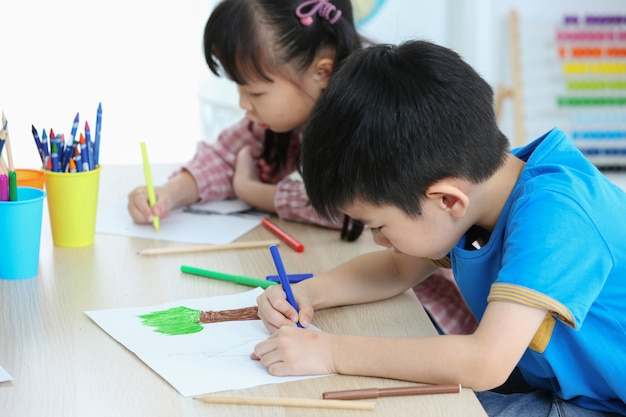 一緒にアジアの就学前の学生は色で描くことによって宿題をします Premium写真