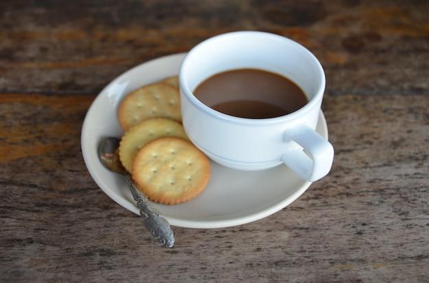 木製の背景に朝食のためのクッキーとコーヒーカップ Premium写真