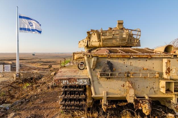イスラエルの廃止されたイスラエルセンチュリオン戦車の横に飛んでイスラエルの旗 Premium写真
