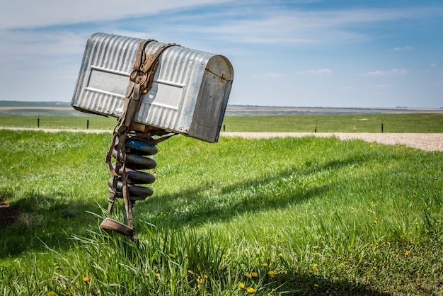 カナダのサスカチュワン州の田園地帯でそれを包んだブライドル付き牧場主の古い金属製メールボックス Premium写真