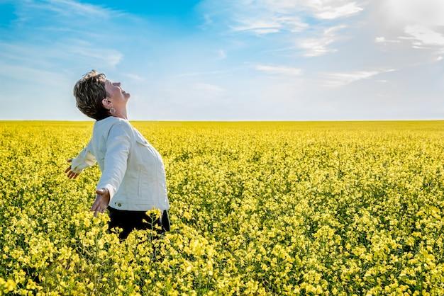 満開の菜の花畑で育った腕で立っている若い白人女性 Premium写真