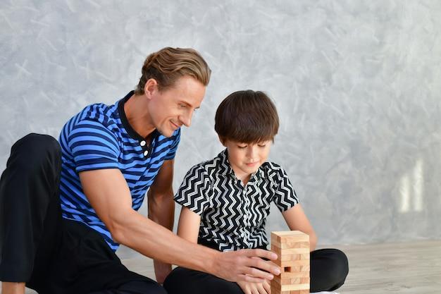 家族の概念。家族は家で幸せです。お父さんと息子は家で楽しく遊んでいます。 Premium写真
