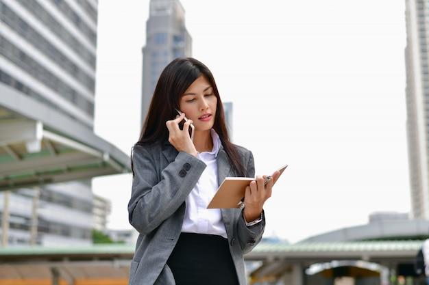 ビジネスコミュニケーションの概念若いビジネスマンは携帯電話を使用して通信します。 Premium写真