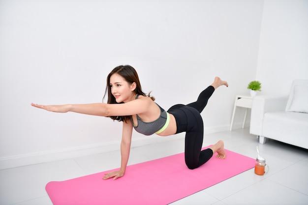 Красивая девушка тренируется в своем доме. Premium Фотографии