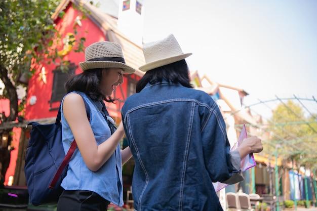 美しい女の子が地図上に観光地を見つけています。 Premium写真