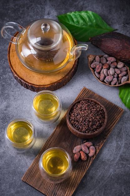 ホットカカオティー。カカオ豆フレークで作られた新鮮なホットチョコレートハーブティーは、フラボノイドと抗酸化物質が豊富で、グラスで提供されます。セレクティブフォーカス Premium写真
