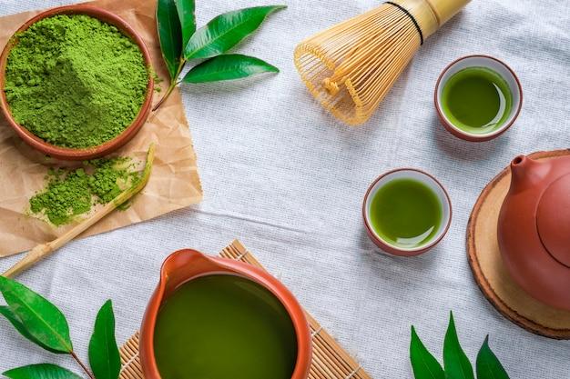テーブルの上のセラミック皿の葉と緑茶粉末、マチャ茶道のための竹で作られた日本のワイヤー泡立て器 Premium写真