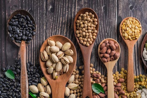 Смешайте орехи в деревянной ложке. Premium Фотографии