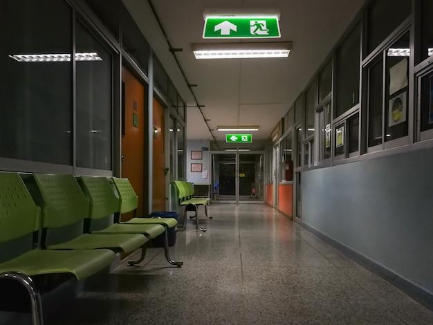 Зеленый знак аварийного выхода в больнице, показывая путь к побегу ночью Premium Фотографии