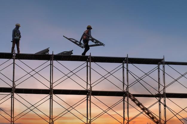 足場と建物、建設工場の足場と建設現場で作業する人 Premium写真