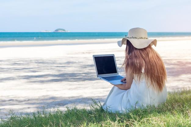 ビーチ、海に取り組んでいる女の子フリーランサーに座っているドレスでラップトップを使用して若いアジア女性 Premium写真