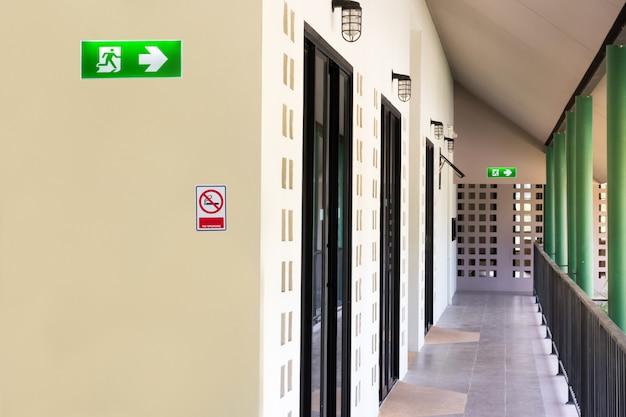 脱出する方法を示すドアの建物の建設の上にインストールする緑の非常口サイン Premium写真