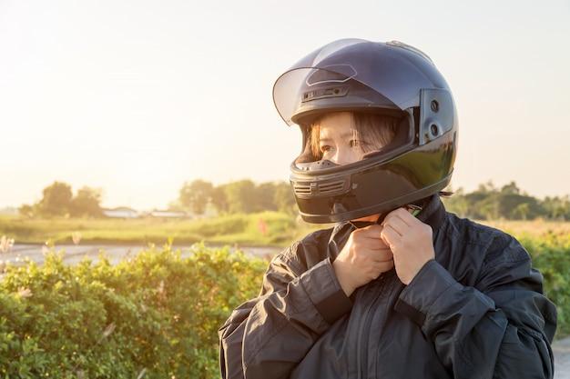Азиатская женщина с шлемом и носить и закрепить, прежде чем ехать большой мотоцикл велосипед на дороге для безопасности Premium Фотографии