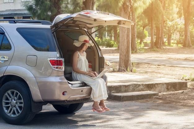 若いアジア人の女性が車の中で座っているドレスでラップトップを使用して Premium写真