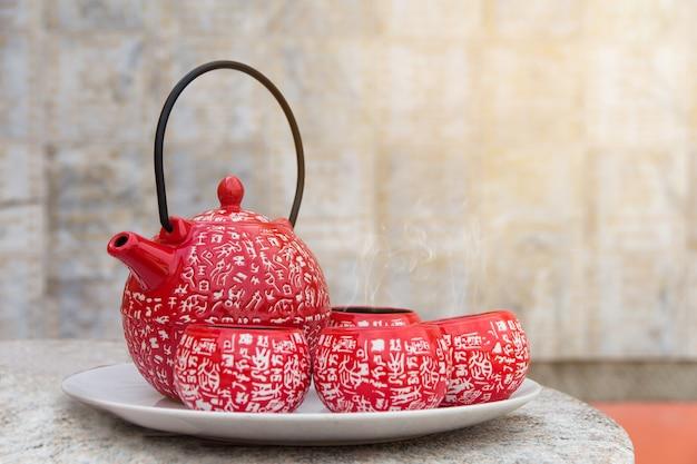Чайный тормозной набор, красные чашки горячего чая на деревянном столе Premium Фотографии
