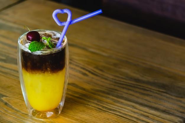 ミックスフルーツジュースと木製のテーブルの上のコーヒー Premium写真