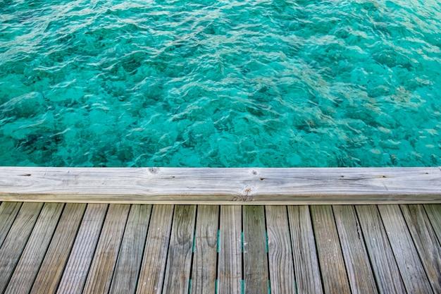 モルディブの美しく澄んだ海の上の木製のバルコニー Premium写真