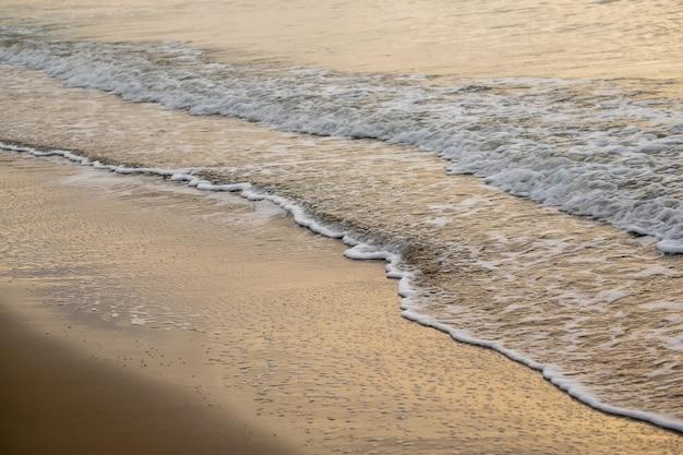 日没時間の砂浜に光沢のある熱帯海の波 Premium写真