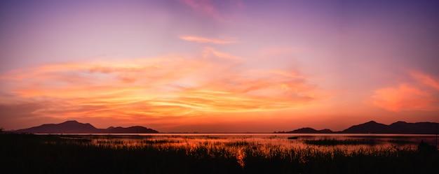夕暮れの空と湖の上の夕日のパノラマビュー Premium写真